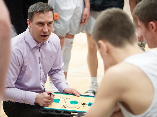 North Kitsap basketball coach Scott Orness draws up a play Saturday against Cheney.