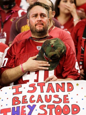 An Arizona Cardinals fan sheds tears during the National Anthem on the 15th anniversary of 9/11 before the Cardinals game against the New England Patriots on Sep. 11, 2016 in Glendale.