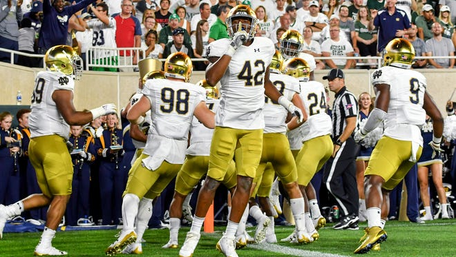 Fighting Irish defensive lineman Julian Okwara (42) gestures to the MSU crowd after Notre Dame scored a touchdown on an interception return in the first quarter against the Michigan State Spartans at Spartan Stadium.