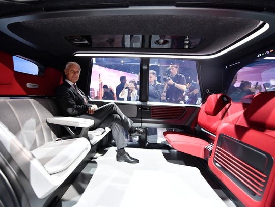 VW CEO Matthias Mueller sits in a Sedric self-driving