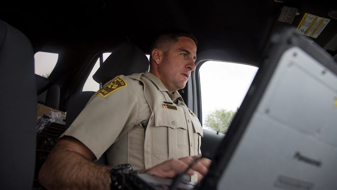 San Juan County Deputy Mike Rietz, a sex offender registration and tracking unit member, works on his computer before conducting a sex registry check Thursday in Aztec.