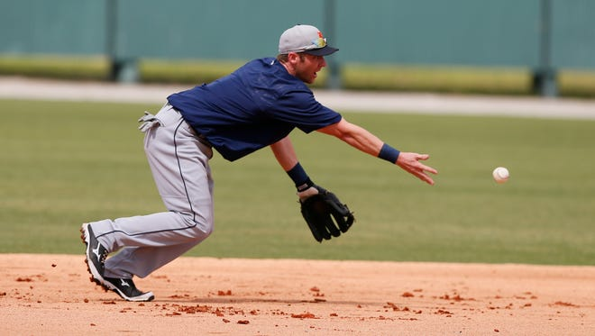 Detroit Tigers infielder Andrew Romine tosses a ball to second base during practice Monday, Feb. 23 2015, in Lakeland, Fla.
