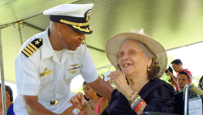 U.S. Naval Base Commanding Officer Capt. Andy Anderson greets World War II survivor Isabel Alvarez Siquenza at a memorial mass held at Sumay Cemetery in U.S. Naval Base Guam on July 20 as part of the Guam's 71st Liberation Day festivities.