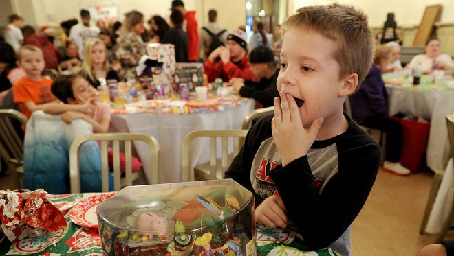 Gage Hess, 7,  of York reacts to presents being opened at his table at the A Christmas Smile event at the Elks Club in York.