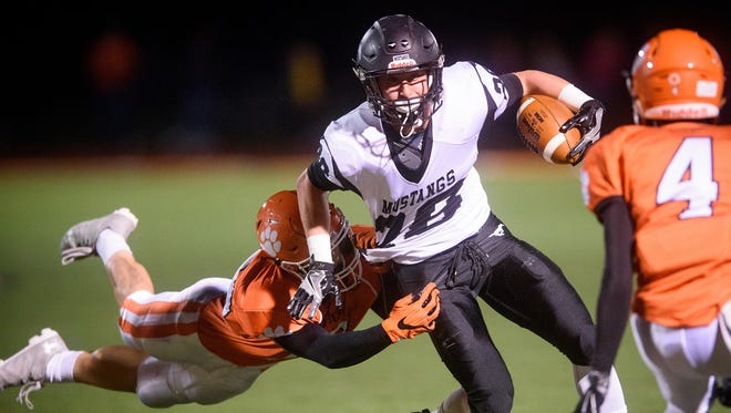 South Western running back Drew Hartlaub (28) powers through a diving tackle by Central York's Cortland Sperry (70) as Obi Anyatonwu (4) approaches in a YAIAA football game at Central York on Friday. Hartlaub scored two touchdowns on the evening, and South Western won 14-11.