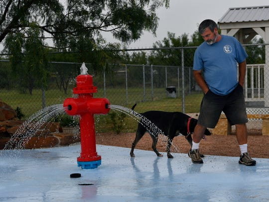 Spencer Butcher leads one of his guests, Wrigley, around the splash pad he installed at his pet boarding business, My Pet Butler. Butcher installed the doggy splash pad at the beginning of the summer.