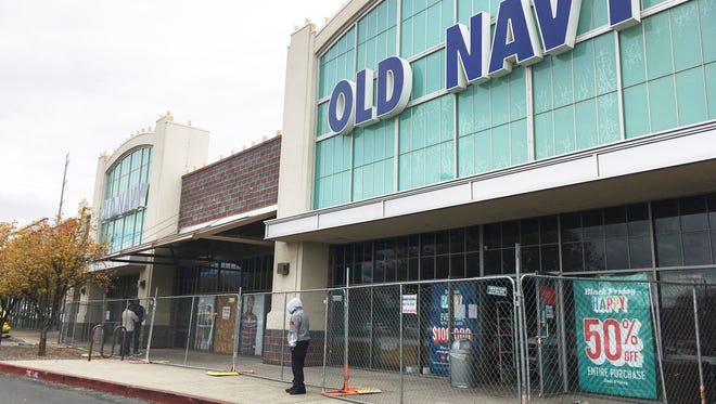 Workers clean up an Old Navy store in Albuquerque on Monday, Nov. 28, 2016, two days after authorities say an explosive device damaged the store.