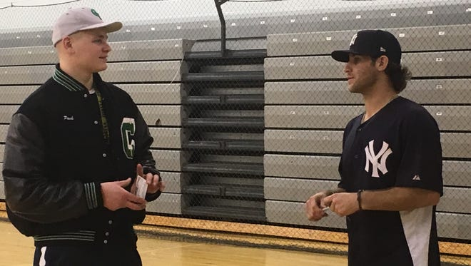 Former state champion pitcher Travis Hissong talk with Clear Fork junior Pauley Francisco following Sunday's pitching clinic