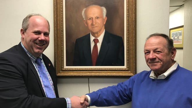ShopRite of Carteret Vice President of Operations Jonathan D'Orsi, left, and Leonard-Sitar recently spearheaded a $3 million renovation of their store. They are pictured with a portrait of John Sitar, the store's founder and their father and grandfather.