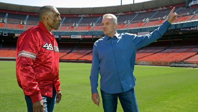 In this June 4, 2014, file photo, San Francisco 49ers Hall of Fame quarterback Joe Montana, right, and retired running back Roger Craig, left, reminisce while walking through Candlestick Park in San Francisco.  As the Super Bowl returns to the technology-rich, football-crazed Bay Area for the first time since 1985 to celebrate its 50th edition, Craig cannot help but reflect on how different the NFL's biggest show has become. (AP Photo/Eric Risberg, File)