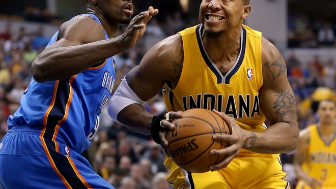 Pacers David West drives on the Thunder's Serge Ibaka in the first half of their game Sunday, April 13, 2014, afternoon at Bankers Life Fieldhouse