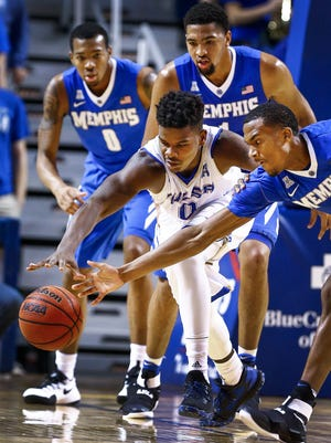 University of Memphis teammates Jeremiah Martin  (right) battles Tulsa University guard Junior Etou (left) for a loose ball during first half action at the Donald W. Reynolds Center in Tulsa, Oklahoma.