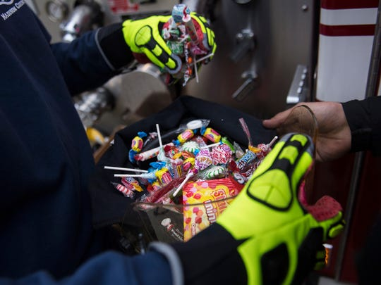 Madison County Firefighter Jacob Ewell scoops handfuls of candy into a helmet held by fellow firefighter Daniel Beck on Saturday, Oct. 28, 2017, during the 10th annual Jackson-Madison County Trunk or Treat at the Ballpark at Jackson.