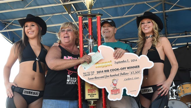 Donna Rice with Desperado's from Hinckley, Ohio, accepts the winning trophy and a check for $7,500 from John Ascuaga's Nugget President and CEO Carlton Geer on Monday afternoon at the Best in the West Nugget Rib Cook-off in Sparks.