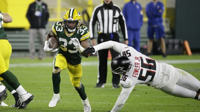 The Packers' Aaron Jones (33) runs past the Atlanta Falcons' Dante Fowler Jr. (56) during the second half on Monday night in Green Bay, Wis.