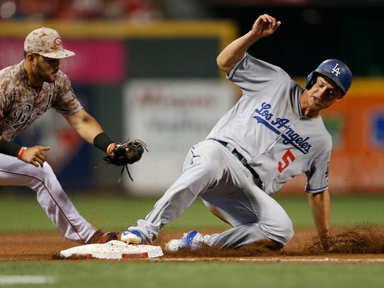 Los Angeles Dodgers' Corey Seager (5) slides safely into third, advancing on a single by Micah Johnson, as Cincinnati Reds third baseman Eugenio Suarez attempts the tag on the Dodgers' Corey Seager during the ninth inning of a baseball game, Friday, Aug. 19, 2016, in Cincinnati. The Reds won 9-2.