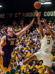 UVM's Anthony Lamb, right, pops a shot over Albany's Mike Rowley during the first half the 2017 America East men's basketball championship game in March.