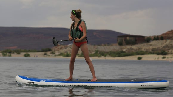 Kylee Sorensen, of St. George, tries out a stand-up paddleboard at Quail Creek Reservoir State Park in Hurricane.