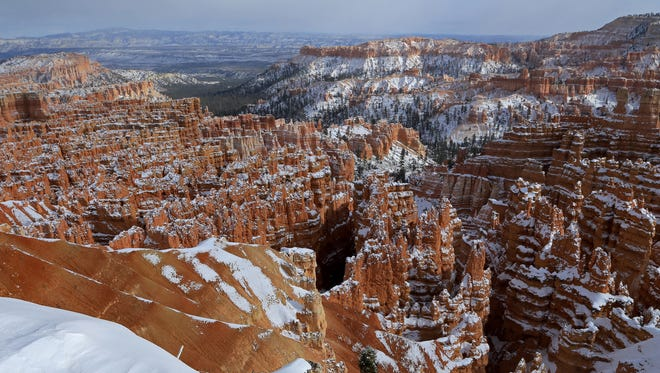Snow blankets the rim of Bryce Canyon and caps its distinctive hoodoos in the amphitheater below.
