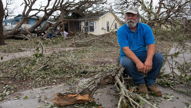 David Graves takes a break from clearing trees from around his home along Palm Street a day after Hurricane Harvey made landfall in Fulton, Texas.