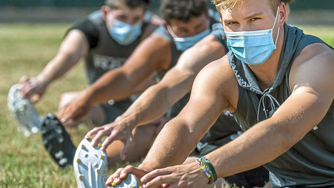 In this file photo from July 6, 2020, Pine-Richland High School quarterback Cole Spencer, right, and teammates stretch during their first practice of the season, at Richland Elementary in Pine-Richland Township near Warrendale, Pa. The Pennsylvania Interscholastic Athletic Association (PIAA) governing body for Pennsylvania interscholastic sports signaled that it's seriously considering moving ahead with the fall season despite the governor's recommendation that all youth athletics be canceled until 2021.