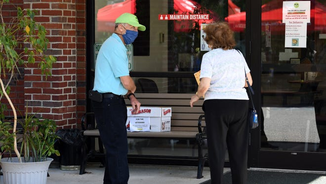 Bill Neeb, left, volunteer project leader, talks with a client Tuesday before she meets with a tax preparer at the AARP Income Tax Program at the Billerica Council on Aging.   [Daily News and Wicked Local Staff Photo / John Walker]
