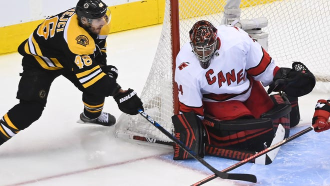 Carolina Hurricanes goaltender Petr Mrazek (34) makes a save on a wrap-a-round attempt by Boston Bruins center David Krejci (46) during the third period of an NHL Eastern Conference Stanley Cup hockey playoff game in Toronto, Wednesday, Aug. 12, 2020.