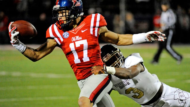 Mississippi tight end Evan Engram (17) catches a pass as Mississippi State defensive back Jay Hughes (3) tackles him during the second half of an NCAA college football game in Oxford, Miss., Saturday, Nov. 29, 2014. No. 18 Mississippi beat No. 4 Mississippi State 31-17. (AP Photo/Thomas Graning)