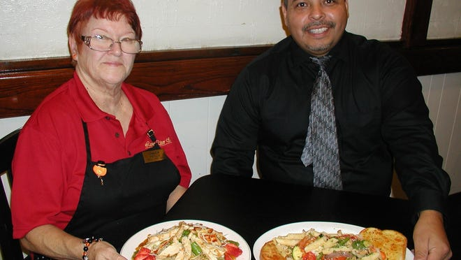 Lamp Liter Inn Grille manager Phyllis Patterson and banquet manager Nick Galvan with a couple of the restaurant's popular dishes, Chinese chicken salad, at left and chicken pasta primavera.