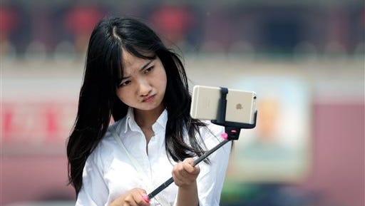 A woman reacts as she uses a selfie stick to take a photo of herself.