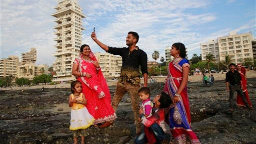 In this Feb. 22, 2016, photo, an Indian family takes a selfie in Mumbai's coastline. India is home to the highest number of people who have died while taking photos of themselves, with 19 of the world's 49 recorded selfie-linked deaths since 2014, according to San Francisco-based data service provider Priceonomics. The statistic may in part be due to India's sheer size, with 1.25 billion citizens and one of the world's fastest-growing smartphone markets. (AP Photo/Rafiq Maqbool)