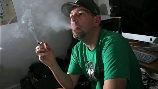 In this March 10, 2016, photo,f ormer U.S. Marine, Mike Whiter smokes marijuana before he starts editing a video project at his home in Philadelphia. A growing number of states are debating whether to legalize marijuana for the treatment of post-traumatic stress disorder. But for an increasing number of veterans, the debate is over. They're using marijuana to alleviate PTSD-induced nightmares and anxiety, even it's banned by the federal government and remains illegal in their state. The trend raises questions about marijuana's safety among a vulnerable group of veterans at a time when major studies have yet to prove the drug's effectiveness. (AP Photo/Mel Evans)