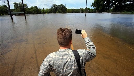 "Staff Sgt. Greg Stevens takes video and photos as he surveys the area on Fisher St. in Lafayette, La., Monday, Aug. 15, 2016. Louisiana Gov. John Bel Edwards says the widespread flooding across south Louisiana has ""presented tremendous challenges,"" but he's proud of the state's response. (Gabe Hernandez/Corpus Christi Caller-Times via AP)"