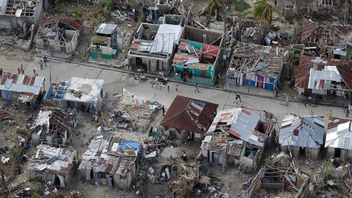 People walk along a street lined with damaged and destroyed houses, in southwestern Haiti, Friday, Oct. 14, 2016. A week and a half after Hurricane Matthew devastated southwestern Haiti, aid is slowly starting to arrive in rural towns, patch-work roofs made from scraps abound, and some families are living in makeshift shelters crafted from the debris.(AP Photo/Rebecca Blackwell)