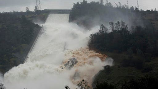 """Water flows through break in the wall of the Oroville Dam spillway in Oroville, Calif. The torrent chewed up trees and soil alongside the concrete spillway before rejoining the main channel below. Engineers don't know what caused what state Department of Water Resources spokesman Eric See called a """"massive"""" cave-in that is expected to keep growing until it reaches bedrock. (AP Photo/Rich Pedroncelli)"""