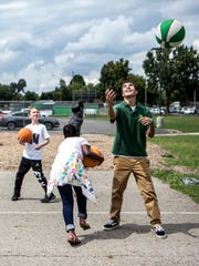 Xavier Gartside, a student at Newark Catholic, shoots hoops with students from McGuffey Elementary School. Students from Newark Catholic have been walking over to the elementary school to lead the kids in games during recess.