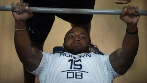 Auburn defensive back Joshua Holsey (15) bench presses