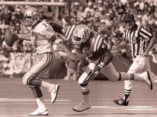 FILE -  In this Sept. 16, 1984, file photo, New England Patriots linebacker Andre Tippett, right, reaches out to haul down Seattle Seahawks quarterback Dave Kriege in Foxboro, Mass. What's certain is that an NFL linebacker's role has changed since Tippett's retirement after the 1993 season ended a 12-year career, all with the New England Patriots, in which he sacked quarterbacks, shadowed receivers, tackled rushers and tried to catch his breath. (AP Photo/Mike Kullen, File)