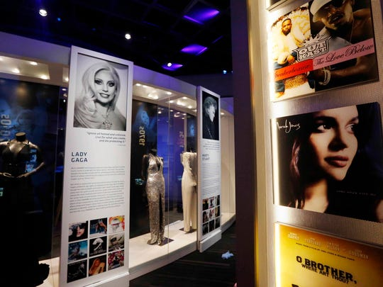 In this Wednesday, March 2, 2016 photo, gowns and outfits of Grammy winning performers are framed by pylons decorated with the covers of the albums of the year winners during each decade in a section of the Grammy Museum Mississippi in Cleveland, Miss. The second and only official Grammy Museum outside of Los Angeles opens Saturday in the Mississippi Delta, cradle of the blues. Organizers chose Cleveland, Miss. - two hours north of the state capitol Jackson - for the nearly $20 million project and promise one of the most advanced museums in the country.  (AP Photo/Rogelio V. Solis)