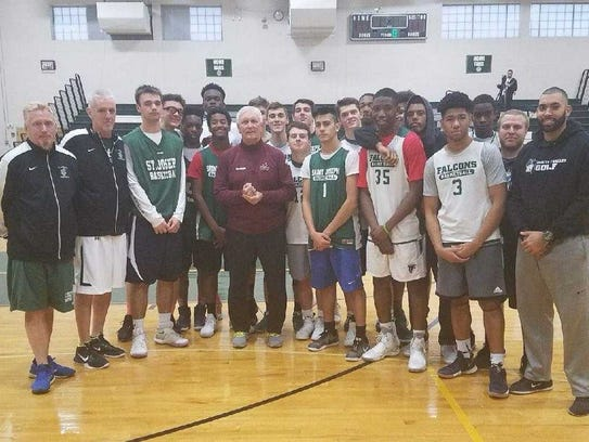 Bob Hurley (center in maroon sweat jacket) poses with