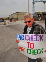 Keith Yanda carries a sign expressing his feelings during an informational picket by Boilermakers Union Local 449 outside Bay Shipbuilding in Sturgeon Bay. The contract between the union and the shipyard expired Sept. 12 and is now in negotiation.