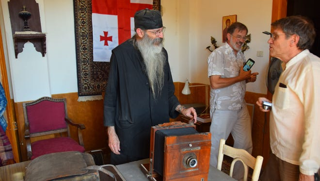 Roger L. Easton Jr. is shown an old camera by Father Justin at the library of St. Catherine's Monastery in Egypt.