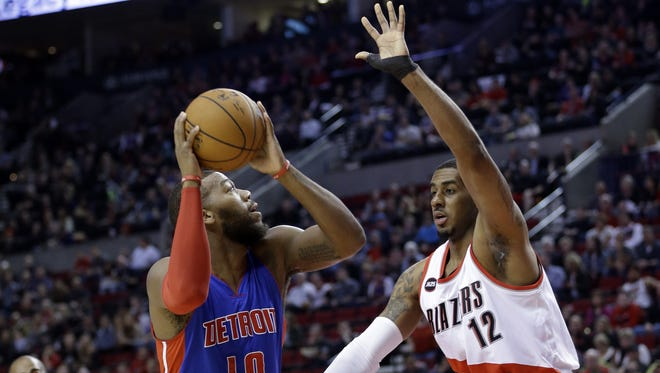 Detroit Pistons forward Greg Monroe, left, looks to shoot against Portland Trail Blazers forward LaMarcus Aldridge during the first half of an NBA basketball game in Portland, Ore., Friday, March 13, 2015.