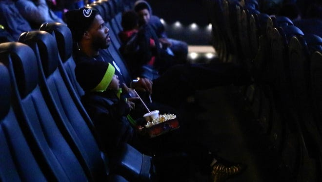 """Briean Boddy-Calhoun, a Cleveland Browns cornerback and Wilmington native, sits with nephew Kyan Berry before the start of """"Black Panther"""" at the Penn Cinema Riverfront & IMAX on Monday. Boddy-Calhoun donated 300 tickets to the film to Project New Start, a nonprofit that organized and gave out tickets."""
