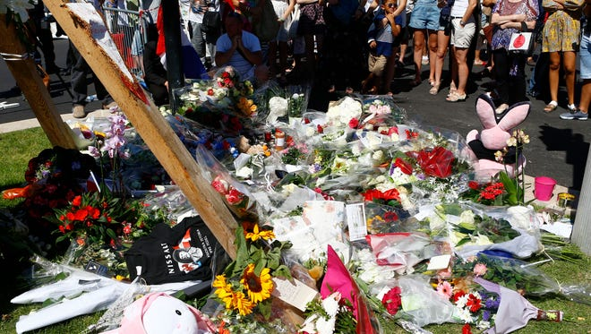 People gather by flowers near the scene where a truck mowed through revelers in Nice, southern France, on July 15, 2016.