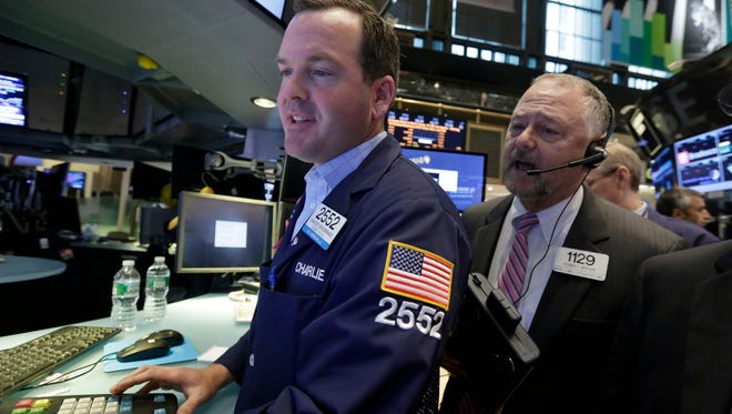 Specialist Charles Boedinghaus, left, and trader Robert Moran, work at a post on the floor of the New York Stock Exchange, during the IPO of Parsley Energy, Friday, May 23, 2014. Founded in 2008, Parsley Energy is an independent oil and natural gas company with operations in the Permian Basin.  (AP Photo/Richard Drew)