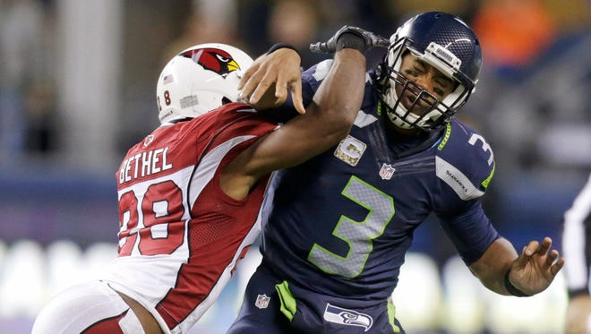 Seattle Seahawks quarterback Russell Wilson (3) is hit by Arizona Cardinals cornerback Justin Bethel just after getting a pass off during the second half of an NFL game on Sunday, Nov. 15, 2015, in Seattle.