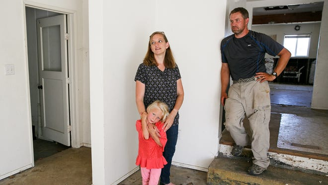 Travis and Denay Tubbs, and their daughter Tiana, 4, stand in their home in Jefferson on Monday, July 16, 2018. The couple, who have seven kids, purchased the property last year but quickly discovered the house was contaminated with high levels of meth. They have been living in trailers in their yard for nearly a year while they wait for the house to be cleaned and remodeled.