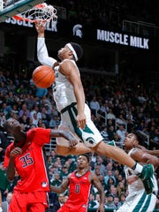 Michigan State's Miles Bridges dunks over Rutgers' Issa Thiam (35).