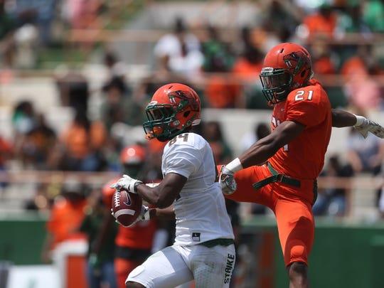 Orange team defensive back Elijah Jones takes down